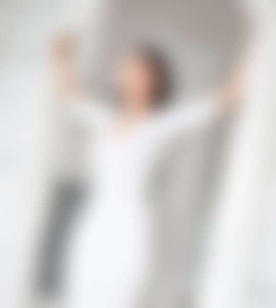 Девушка, сделав упражнения для лица и шеи, стоит у окна и улыбается