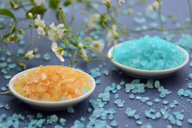 Две тарелочки с оранжевой и голубой солью в окружении зелени — солевой скраб для тела
