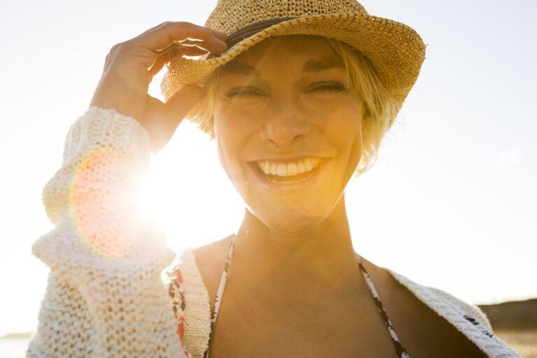 Довольная девушка в соломенной шляпке на закате не думает, что делать, если обгорела на солнце