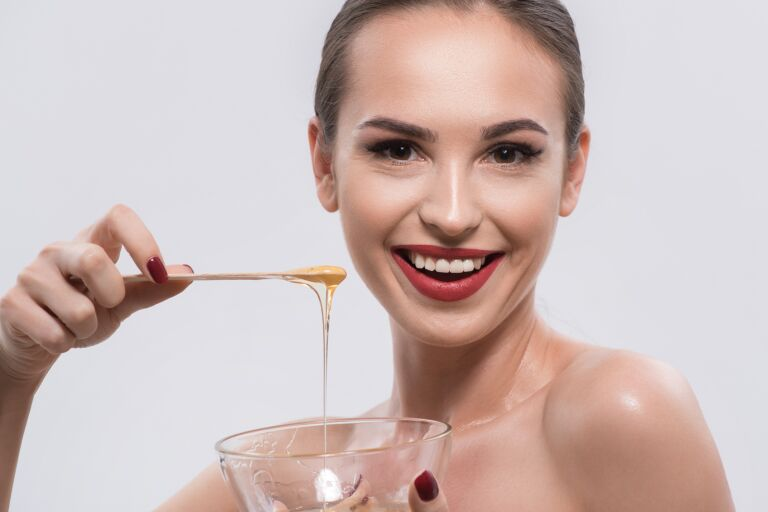 Довольная девушка готовится к медовому массажу лица, достает ложкой из чашки мед и улыбается в камеру