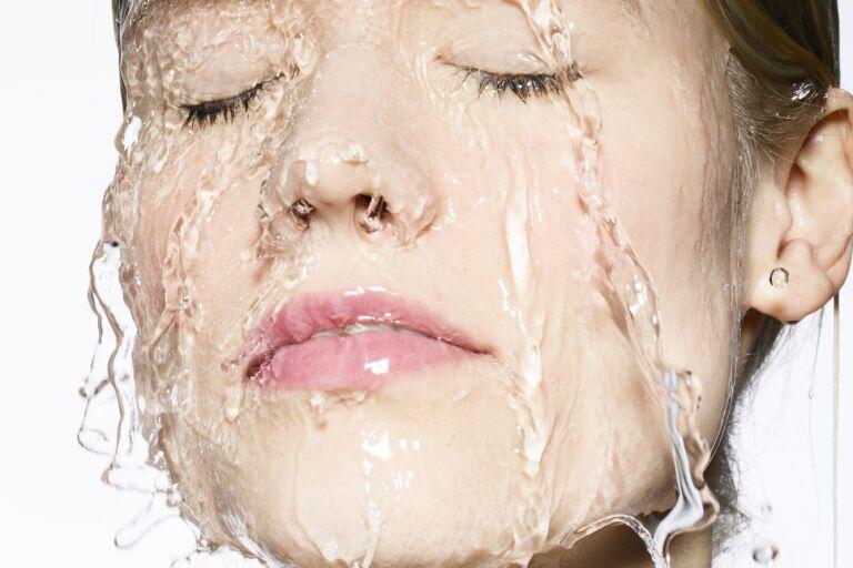 Крупно лицо девушки с закрытыми глазами, по лицу стекает вода