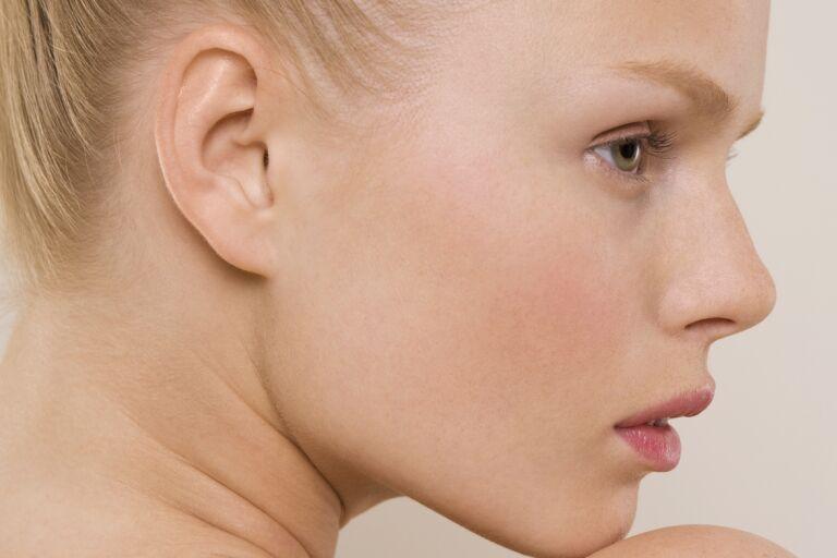 Крупный план девушки-блондинки с кольцами Венеры на шее