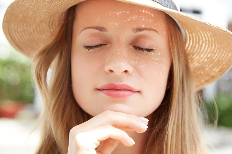 Девушка в соломенной шляпе с бликами солнца на лице прикрыла глаза