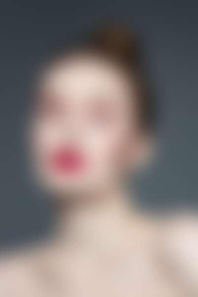 Девушка с красной помадой и маской для лица с глицерином на лице