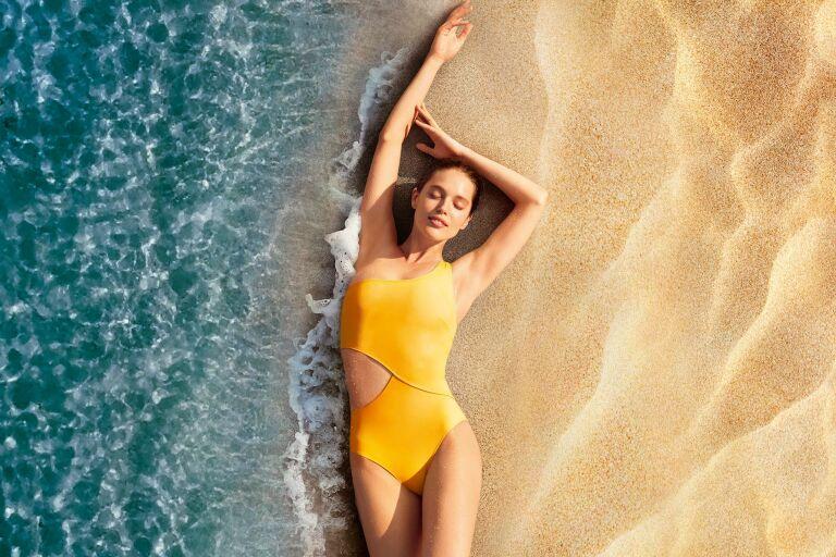 Девушка в ярко-желтом купальнике лежит на пляже, рядом плещется океан