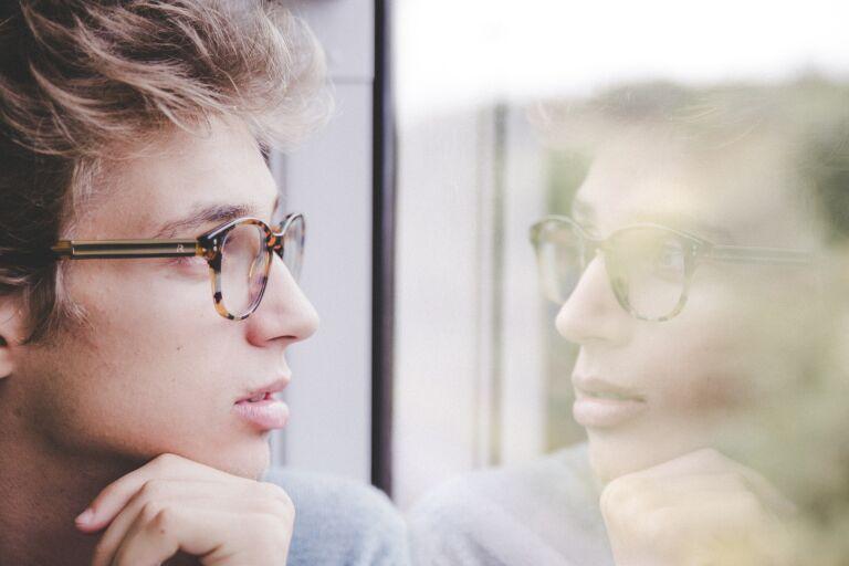 Мужчина смотрит в окно и думает, как убрать второй подбородок