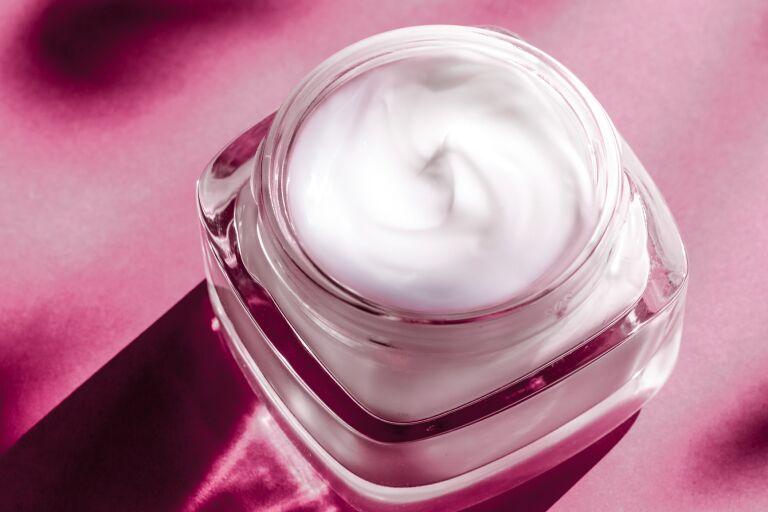 Восстанавливающий крем для лица в открытой стеклянной баночке на розовом фоне