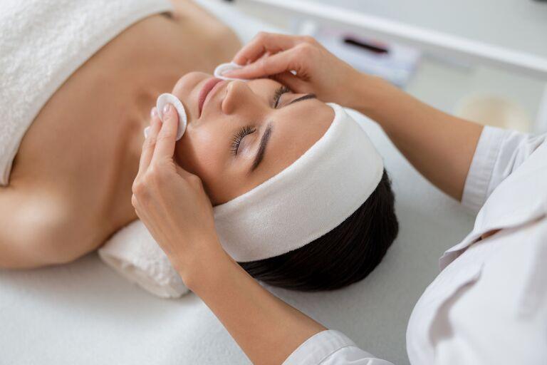Девушка в кабинете косметолога готовится к процедуре микродермабразии