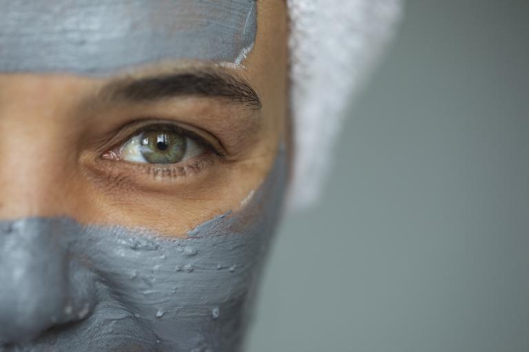 Лицо улыбающейся девушки в маске из голубой глины