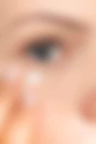 Крупным планом лицо девушки, наносит крем для глаз