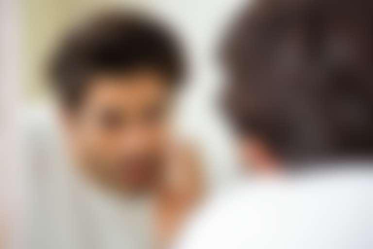 Мужчина рассматривает в зеркале признаки шелушения кожи