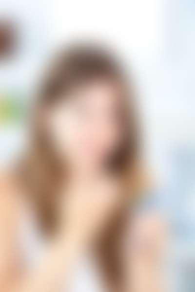 Девушка в белой майке наносит бальзам на обветренные губы