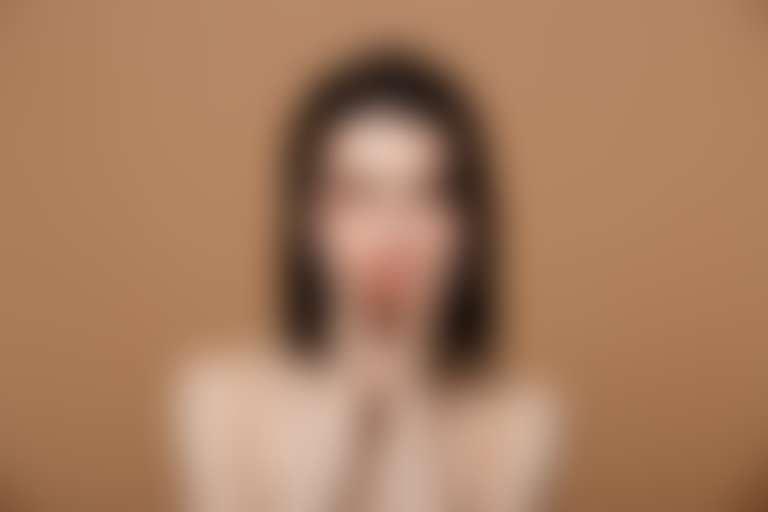 Темноволосая девушка нанесла средство от синяков под глазами