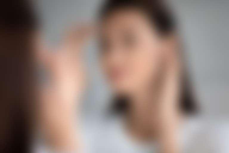 Темноволосая девушка рассматривает себя в зеркале, думает, как омолодить лицо