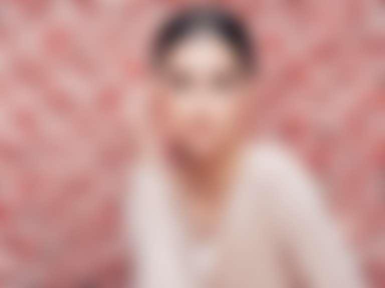 Темноволосая девушка на фоне роз — имидж с одного из рекламных плакатов французской косметики L'Oreal Paris