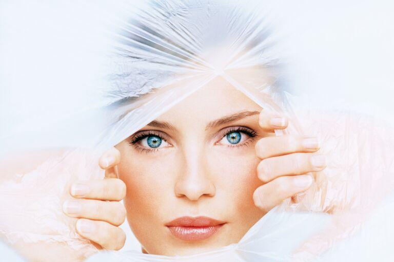 Девушка с красивым лицом прорывает ткань - имитация тканевых масок