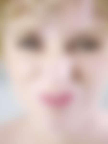 Крупно лицо девушки-блондинки, недовольно сморщившей нос