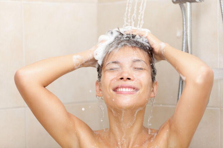 Девушка под душем моет голову с шампунем против перхоти