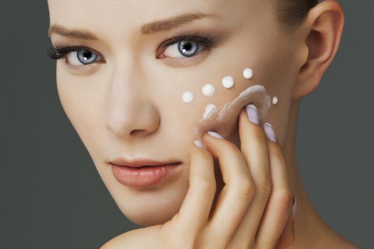 Девушка наносит крем от шелушения кожи лица зимой