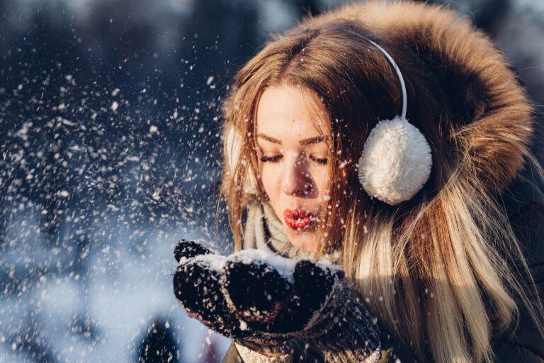 Девушка в зимней шапке и теплых рукавицах сдувает с рук снег и думает, какой крем использовать зимой