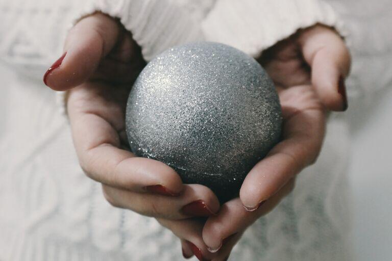 Крупно руки девушки в белом свитере с красным маникюром, сложила ладони в виде сердца и держит в них новогодний серебряный шар