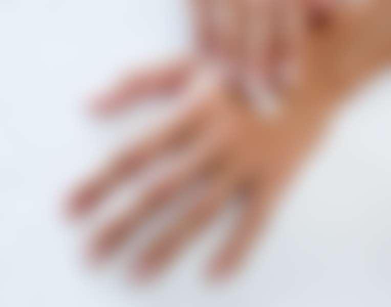 Крупным планом руки, на них наносится крем для рук