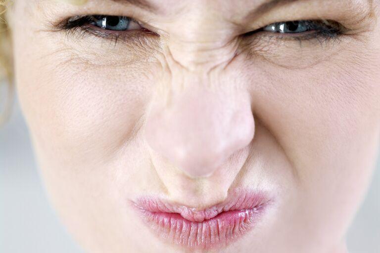 Морщина на переносице у девушки, которая морщит нос