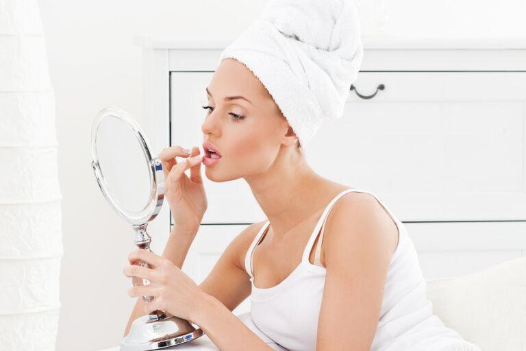 Девушка в белом наносит крем от морщин над верхней губой, глядясь в круглое зеркало.