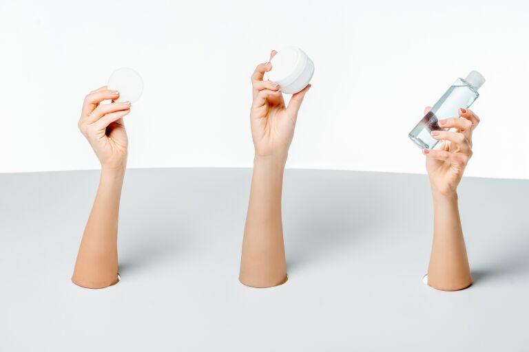 Три руки держат косметические банки с лучшими средствами от прыщей