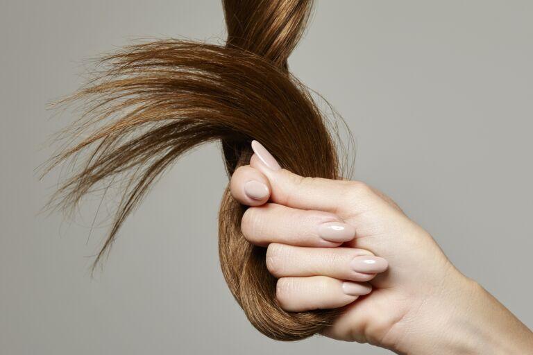 В руке скручена прядь волос