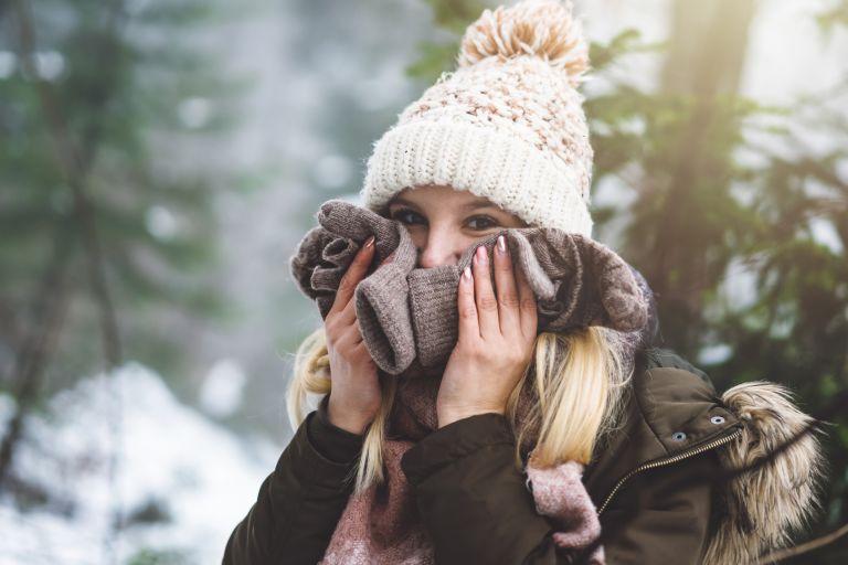 девушка в шапке с помпоном в зимнем лесу закрывает кожу лица варежками