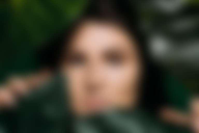 Девушка с органическим кремом на лице выглядывает из-за зеленых листьев фикуса