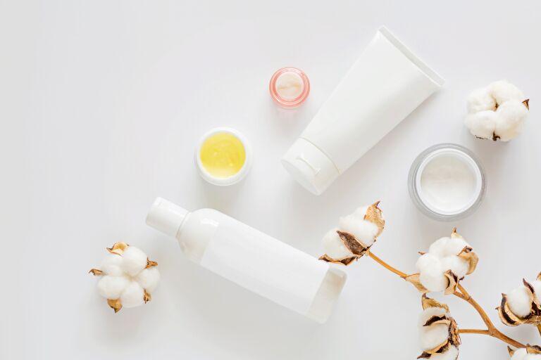 Косметика и цветы хлопка на белом фоне