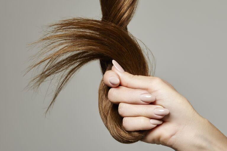 Девушка держит в руках прядь волос с секущимися кончиками