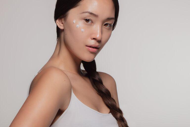 Азиатская девушка с кремом на лице готовится к японскому массажу лица
