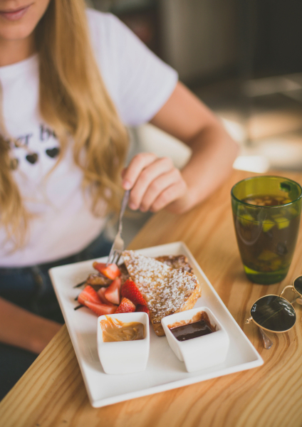 Девушка с жирными волосами ест десерт, рядом стоит коктейль