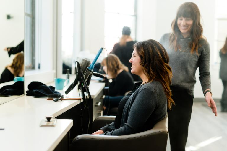 Девушка на приеме у парикмахера-трихолога консультируется по поводу жирных волос