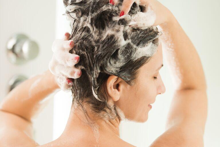 Девушка намыливает голову в душе