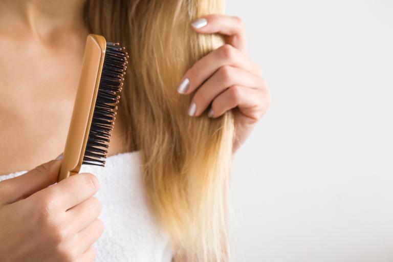 Крупный план – девушка расчесывает длинные волосы расческой с натуральным ворсом