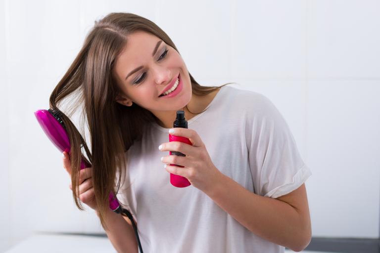 Темноволосая девушка наносит на волосы кондиционер или термозащиту
