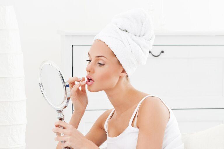 Девушка в белом тюрбане наносит макияж, чтобы поднять уголки губ