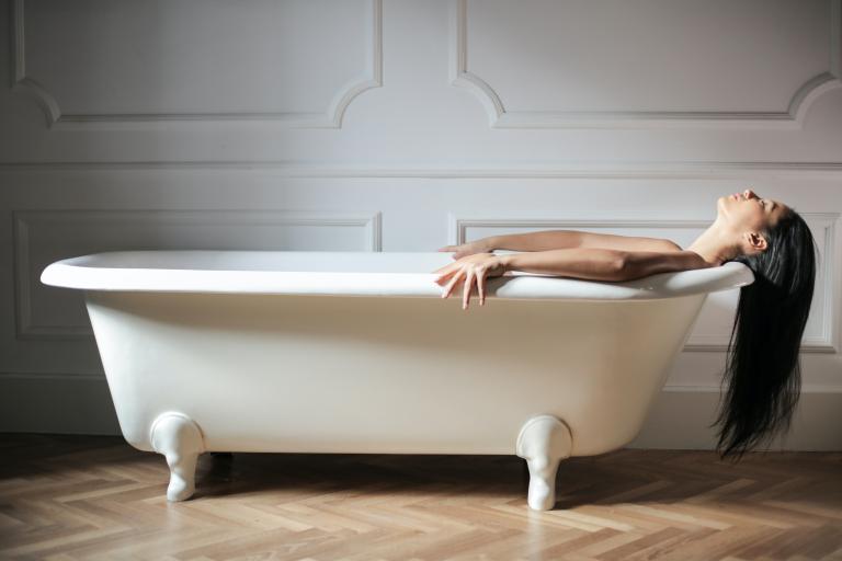 Девушка с тонкими волосами лежит в ванной, сейчас будет их мыть