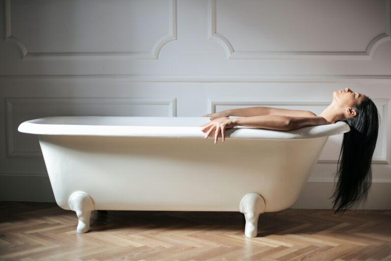 Девушка лежит в белой ванне свесив длинные волосы
