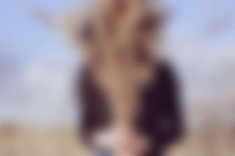 Девушка в темном с букетом колосков - символ сухих волос - на фоне поля с соломой