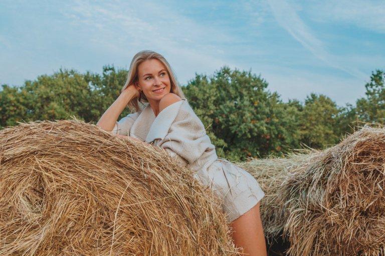 Девушка в поле на фоне стогов с соломой думает, как еще ухаживать за сухими волосами