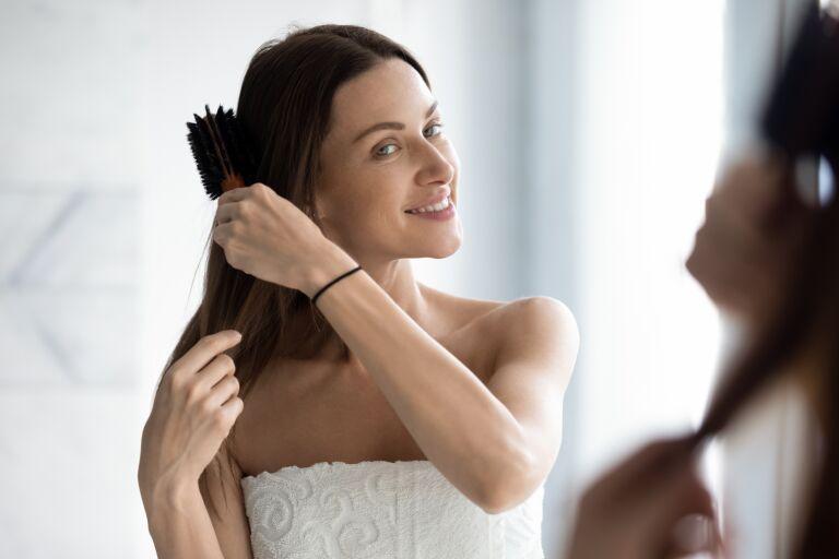 Девушка расчесывает волосы правильно