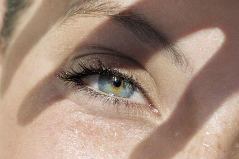 Девушка на фото выбирает лучший крем вокруг глаз