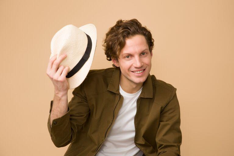 Молодой мужчина с волнистыми волосами и белая шляпа в руке