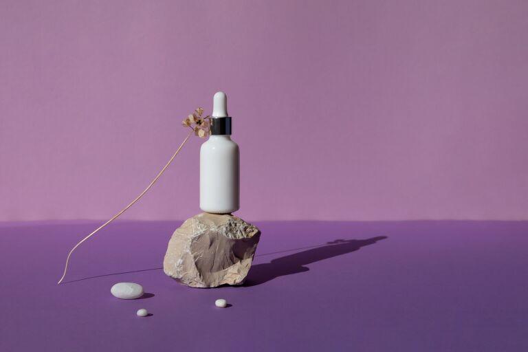 Сыворотка для волос в белом флаконе с пипеткой на камне