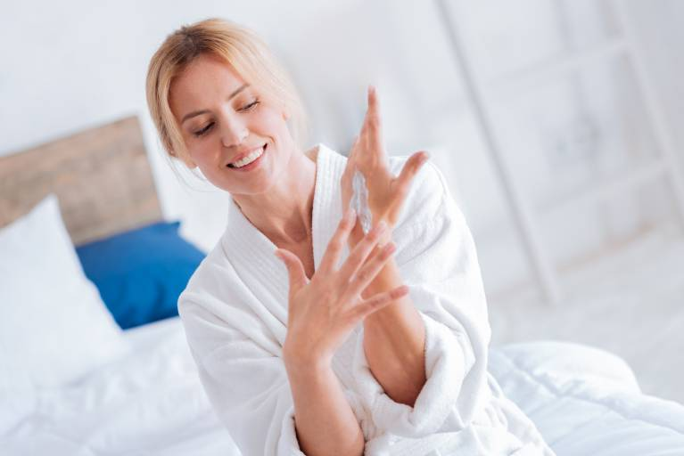 Женщина наносит увлажняющий крем на руки